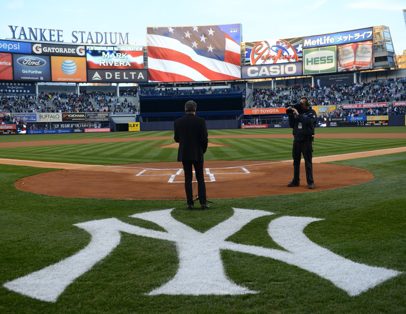 Mark Rivera performs national anthem at Yankee Stadium with American flag on screen