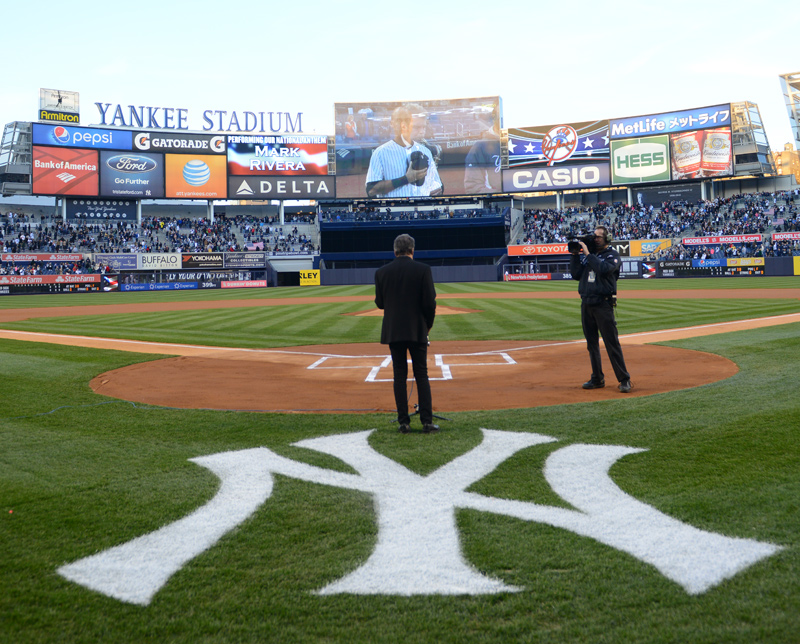 Mark Rivera performs national anthem at Yankee Stadium with shortstop Derek Jeter on screen