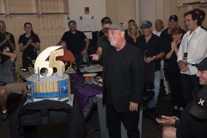 The crew and band surprise Billy Joel backstage at Madison Square Garden with at 65 cake before the show on July 1, 2015
