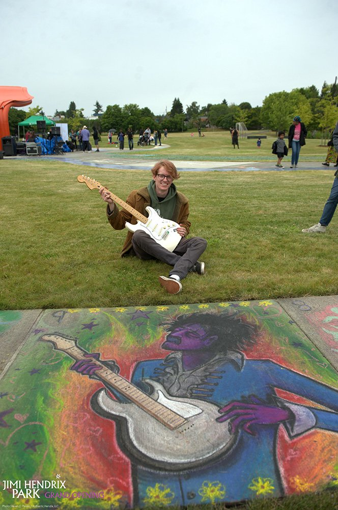 Chalk Art Competition winner Ezra Stansfield with his new Fender Stratocaster sitting alongside his finished masterpiece at grand opening of Jimi Hendrix Park June 17, 2017