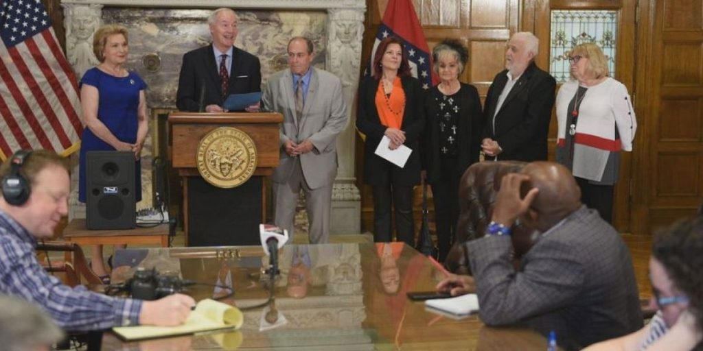 Arkansas Governor Asa Hutchinson signs bill April 11, 2019 for statues of Johnny Cash and Daisy Bates in Arkansas Capitol as Rosanne Cash and family looks on