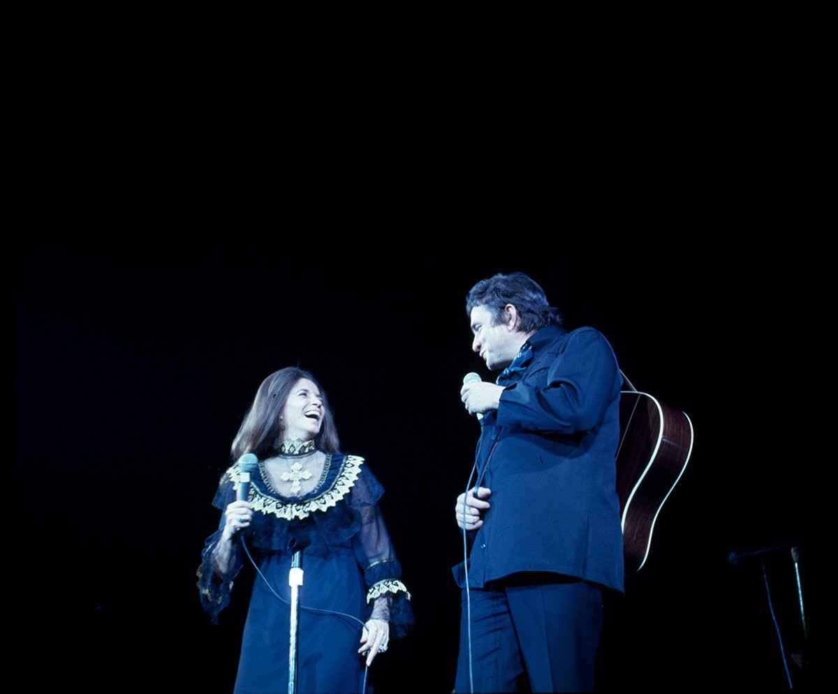 June Carter Cash and Johnny Cash perform live on stage. A photo from this concert would grace the cover of Johnny Cash's 1972 album, 'A Thing Called Love.'