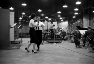 On the dance floor, Betty Comden and Adolph Green, with Bernstein conducting the