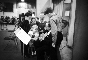 The children gather around the orchestra's guitarist during a break in the recor