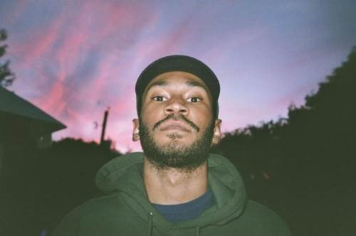 Kaytranada in front of pink and purple sunset