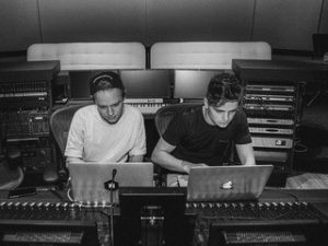 Martin Garrix sits in a studio with another artist
