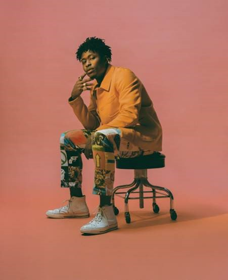 Lucky Daye sits on a black stool in a pastel pink room