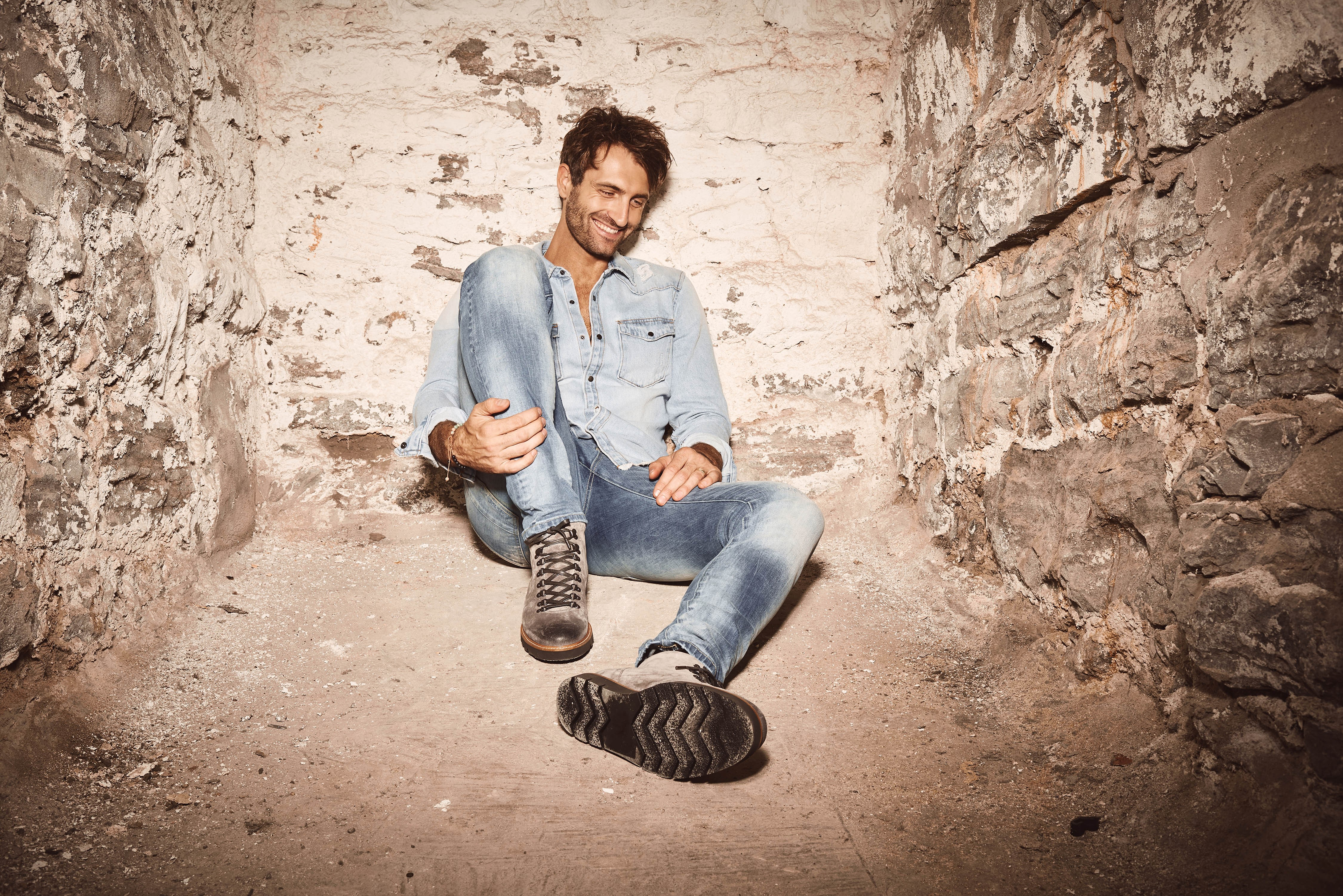 Ryan Hurd sits and poses in a cave