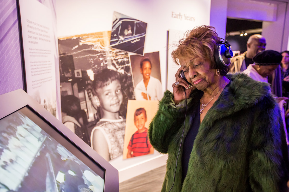 Cissy listening to Whitney on set of headphones featured around the Whitney GRAMMY Museum exhibit at VIP reception October 18, 2018